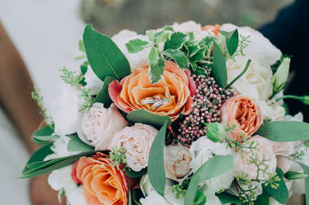 gold wedding rings on a bouquet of flowers Stockfoto - 130101407