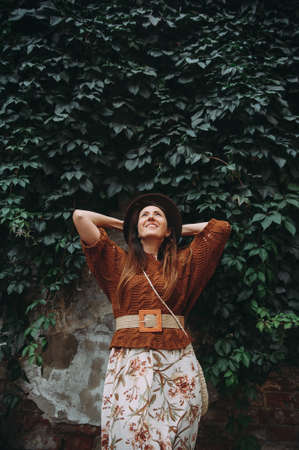 fashion portrait of a stylish brunette in a hat on a background of branches of grapesAutumn trendy look.