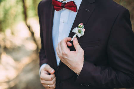 the groom in a suit adjusts the bouton Floral traditional decoration for groom, an accessory on festive wedding suit. Close-up