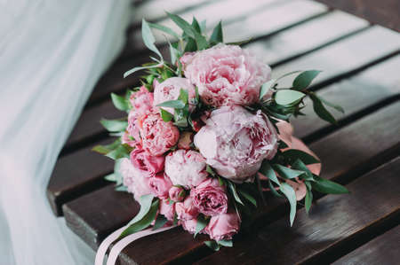 beautiful wedding bouquet of different flowers on a wood background