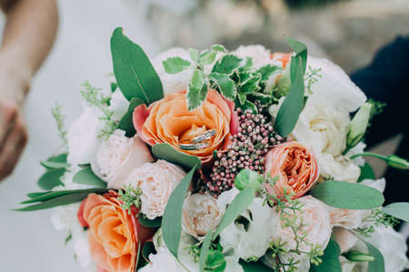 gold wedding rings on a bouquet of flowers