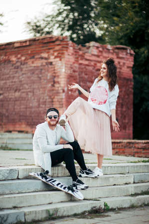 stylish couple guy and girl posing .girl in a skirt. fooling around