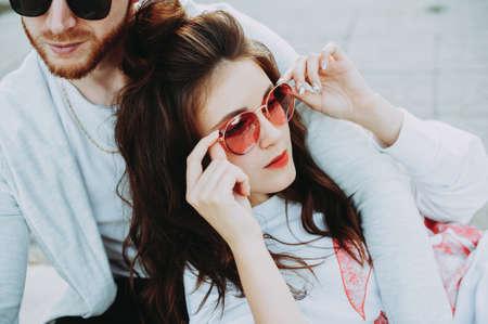 Eyewear concept. Stylish couple. Bearded guy and girl in sunglasses. Stylish casual clothing. Close up. Outdoor shot