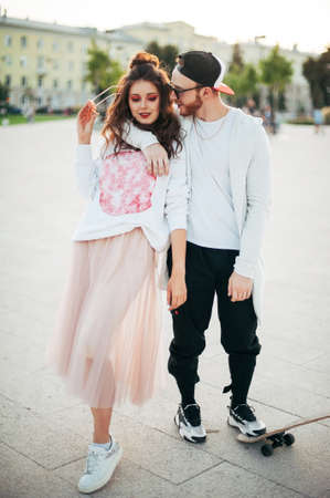 holidays, vacation, love and friendship concept - smiling couple with skateboard riding outdoors