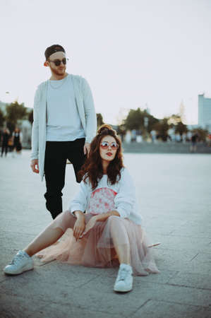 Young fashion elegant stylish couple posing on streets of european city in summer evening weather. a girl with glasses and a guy with glasses, a baseball cap and a beard Stockfoto