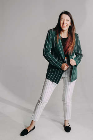 mature stylish brunette in a green jacket posing in the studio