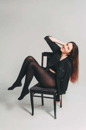 Stylish adult girl sits on a chair in the studio. posing for the photographer. dramatic portrait
