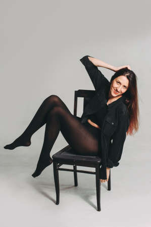 stylish woman with long legs posing on a chair in the studio
