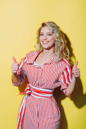 Beautiful woman in red dress smiling extends a hand forward and shows gesture class.Yellow background