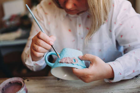 Woman working In her pottery studio. Ceramic workshop. Paint on clay mug in the pottery. Banque d'images