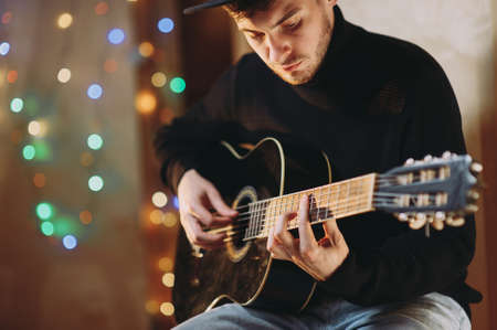 handsome romantic guy plays the guitar. background of lights