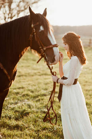 beautiful young bride with a horse on sunset background. girl posing with a horse