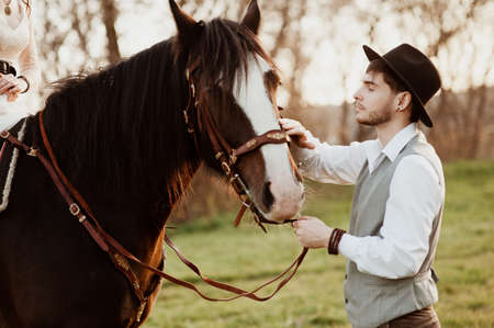handsome groom in a hat stroking a horse. man with a horse 版權商用圖片