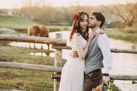 stylish bride and groom on a background of a nature park with horses