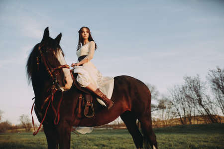 Beautiful stylish bride sits on a horse and looks into the distance. Evening time