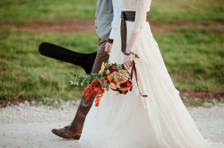 stylish bride and groom walk in nature. the groom with the guitar. close-up