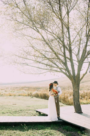 bride and groom posing under a large tree against the background of the river. rustic. loft 版權商用圖片