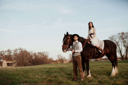 young woman and man walking with a horse in the woods. wedding walk bride and groom 版權商用圖片