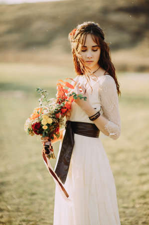 beautiful bride with a wedding bouquet. soft light. field. nature 版權商用圖片