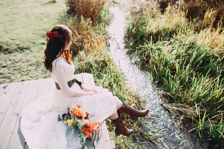 beautiful bride with a bouquet and in boots sits on a bridge against the background of the lake 版權商用圖片