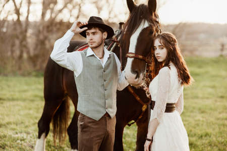 bride and groom with a horse. evening wedding photo shoot in nature