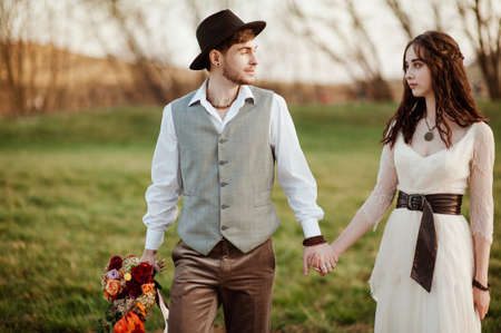 stylish groom in a hat and a bride walk in nature