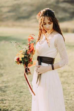 Beautiful bride with a stylish bouquet of different flowers. Rustic Style