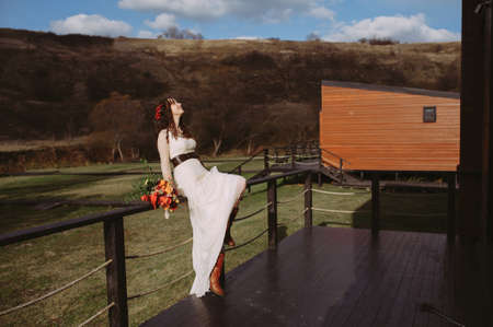 beautiful bride posing at the morning training camp. sitting on a wooden railing against the background of nature