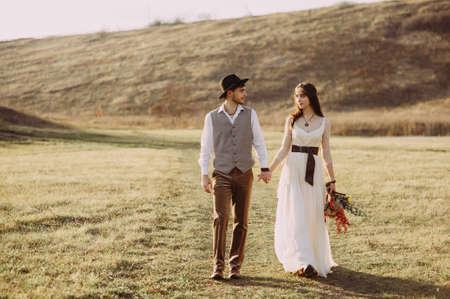 Feliz esposo y esposa. Día de la boda. Hermosa naturaleza. Camine durante la sesión de fotos. Se sonríen el uno al otro. Tomados de la mano