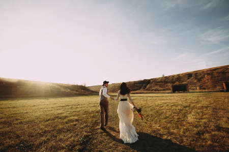Happy husband and wife. Wedding day. Beautiful nature. Walk during the photo session. They smile at each other. Holding hands Stok Fotoğraf