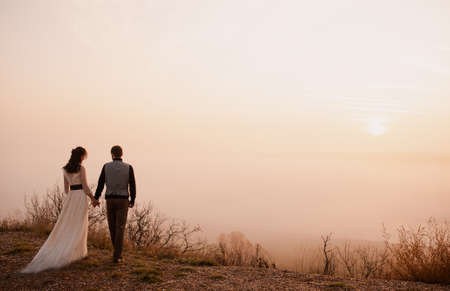 Beautiful stylish couple in love at sunset on a background of fog. love story. silence. frame from the movie Stock Photo