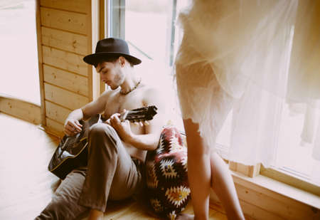 guitarist plays his girlfriend a guitar in a wooden house. Couple in love concept. Banco de Imagens
