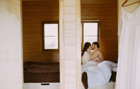 couple in love kiss on bed in a wooden house