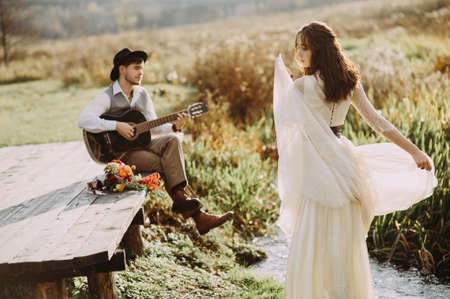 Romantic guy in a hat plays the guitar for his girlfriend on a wooden bridge near the river. girl dancing
