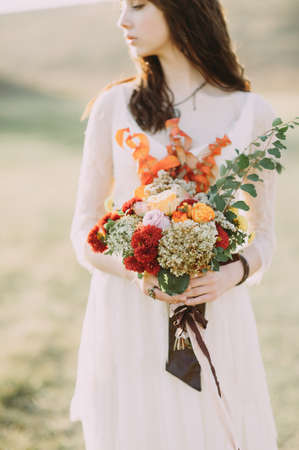 A bride holds rustic wedding bouquet consisting of different flowers. Decoration Artwork. Soft. selective focus