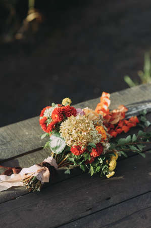 beautiful wedding bouquet of different flowers lies on a wooden bridge