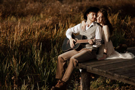 Romantic guy in a hat plays the guitar for his girlfriend on a wooden bridge near the river