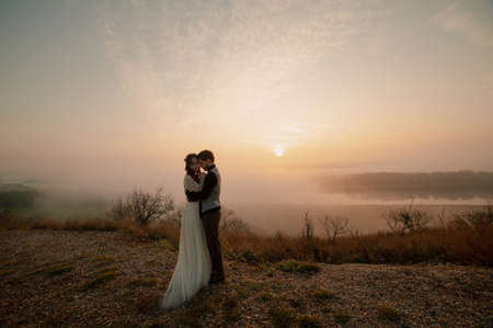 beautiful wedding couple in love bride and groom on the background of the sunset sky. hug Banco de Imagens