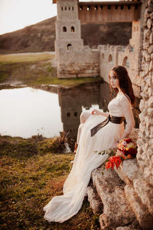 Beautiful bride in a long white dress with a belt. Woman with a bouquet of flowers. Lady sits near the river against the backdrop of a stone castle