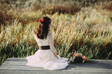 beautiful young bride with flowers in her hair sits on a bridge. boho style. rustic Banco de Imagens
