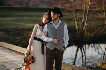 bride and groom on the background of the river. bride with a bouquet. the groom in the hat. rustic style. boho Banco de Imagens