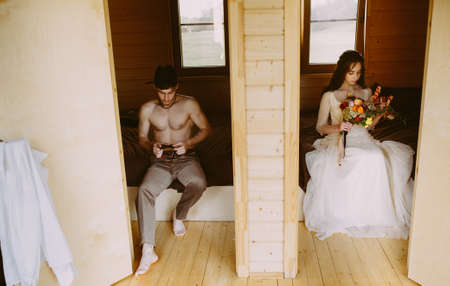 wedding preparations of the bride and groom. sitting on the bed. the groom holds a bow tie in his hands