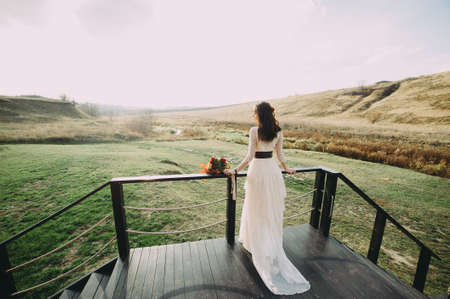 beautiful young bride in a beautiful dress stands on a wooden bridge against the background of the river. flowers in the hair. boho style