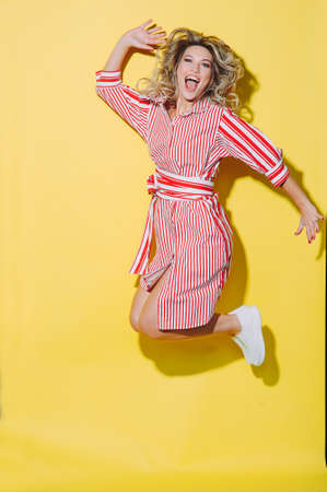 concept happy emotional young woman in red summer dress and hat jumping and laughing on yellow background Banco de Imagens