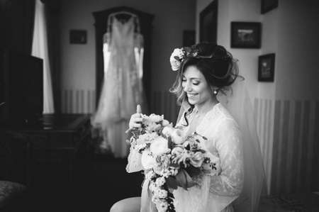 beautiful bride with a bouquet of flowers posing in bed on the morning preparations. flowers in the hair. black and white photo. BW Banco de Imagens