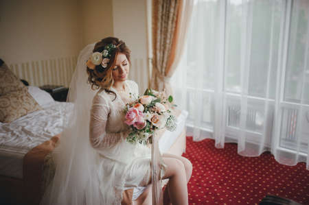 beautiful bride with a bouquet of flowers posing in bed on the morning preparations. flowers in hair. Bride boudoir. Wedding morning. Banco de Imagens