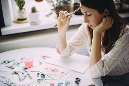 Beautiful girl artist paints with watercolors in a bright studio. Art. Drawing Stockfoto