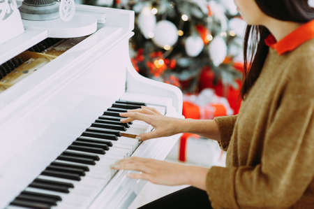 Brunette plays on a white piano against the background of a Christmas tree. Hands close-up