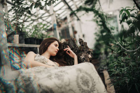 beautiful girl lies in a greenhouse. posing for a photo shoot. languid look. a tropical forest