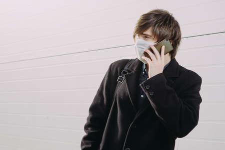 A guy in a protective medical mask calls on his cell phone. Virus protection. Coronavirus
